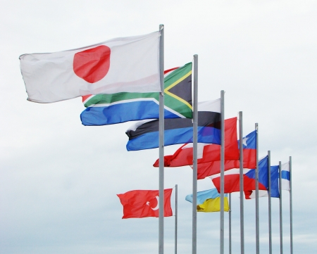 flagpoles: flags of several countries on flagpoles against the sky
