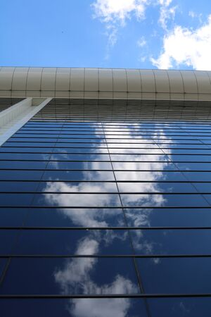 transom: The glass wall of business center like a mirror reflecting the sky with clouds Stock Photo