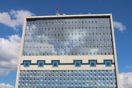 transom: The glass wall of business center like a mirror reflecting the sky with clouds Editorial