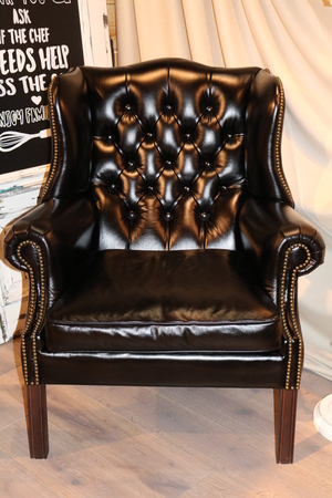 Wooden black armchair in an interior upholstered in natural leather