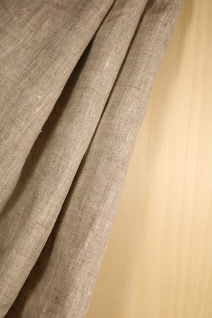 Linen unpainted fabric with folds on the background of wood Stock Photo