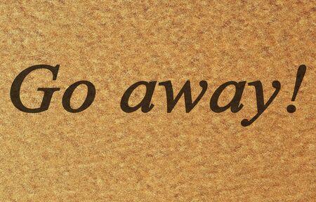 unwelcome: door mat with go away written on it