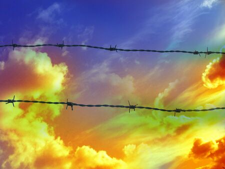 barbed wire on a sky with some clouds in it photo