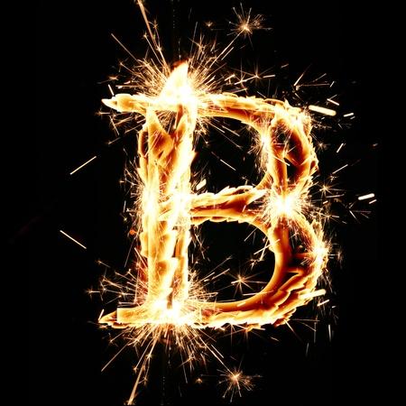 burning letter: sparkling font: letter B on a dark background Stock Photo