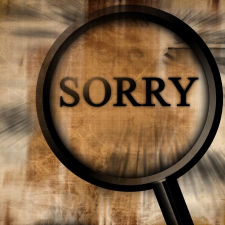 sorry with magnifier on a brown background photo