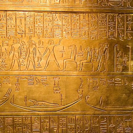 egyptian hieroglyphs on a shiny golden panel photo