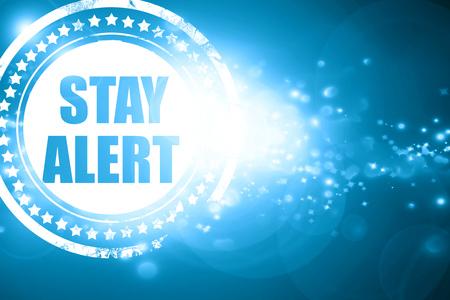 safety slogan: Glittering blue stamp: stay alert Stock Photo