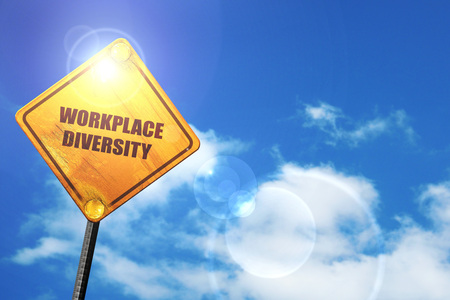 workplace diversity: yellow road sign with a blue sky and white clouds Standard-Bild