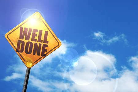 community recognition: well done: yellow road sign with a blue sky and white clouds Stock Photo