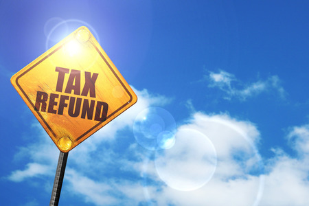 tax refund: yellow road sign with a blue sky and white clouds