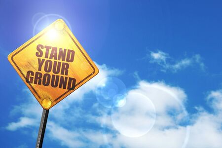 self harm: stand your ground: yellow road sign with a blue sky and white clouds