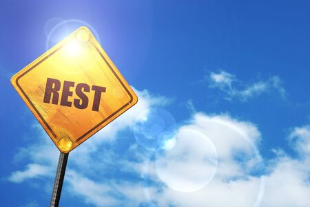 rest: yellow road sign with a blue sky and white clouds Stock Photo