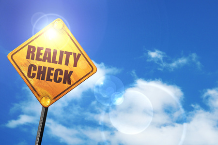 reality check: yellow road sign with a blue sky and white clouds