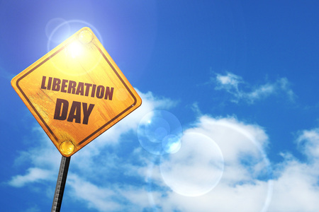 liberation: liberation day: yellow road sign with a blue sky and white clouds Stock Photo