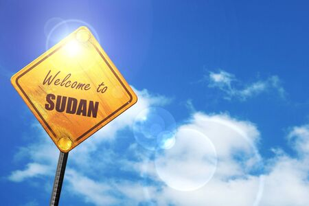trip hazard sign: Welcome to sudan card with some soft highlights: yellow road sign with a blue sky and white clouds Stock Photo