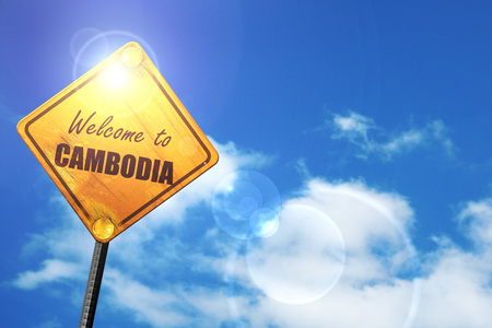 trip hazard sign: Welcome to cambodia card with some soft highlights: yellow road sign with a blue sky and white clouds Stock Photo