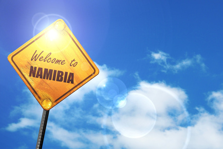 trip hazard sign: Welcome to namibia card with some soft highlights: yellow road sign with a blue sky and white clouds