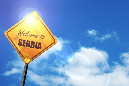 trip hazard sign: Welcome to serbia card with some soft highlights: yellow road sign with a blue sky and white clouds