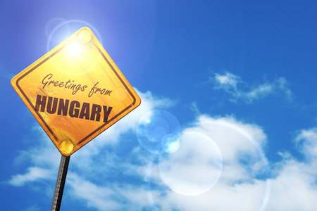 Greetings from hungary card with some soft highlights: yellow road sign with a blue sky and white clouds