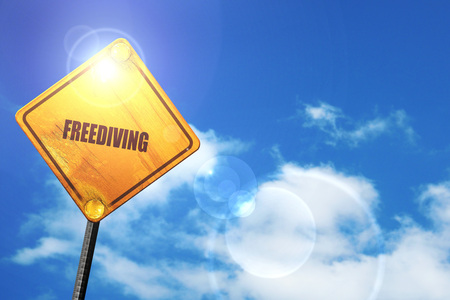 freediving: freediving sign background with some soft smooth lines: yellow road sign with a blue sky and white clouds
