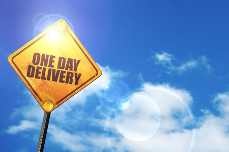 consignment: one day delivery: yellow road sign with a blue sky and white clouds Stock Photo