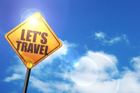 trip hazard sign: lets travel: yellow road sign with a blue sky and white clouds Stock Photo
