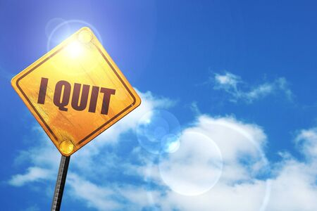 i quit: yellow road sign with a blue sky and white clouds Banco de Imagens