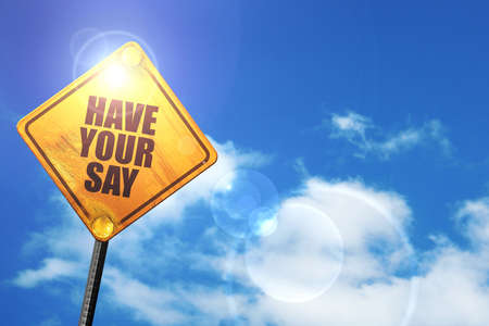 have your say: yellow road sign with a blue sky and white clouds