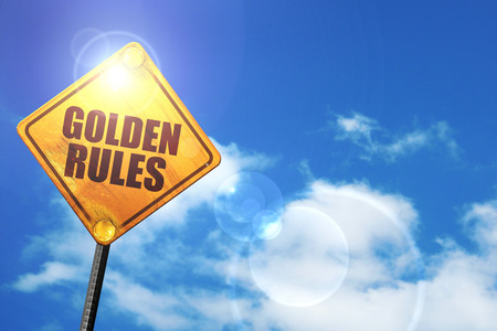 golden section: golden rules: yellow road sign with a blue sky and white clouds Stock Photo