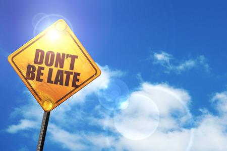 llegar tarde: no llegar tarde: cartel amarillo con un cielo azul y nubes blancas Foto de archivo