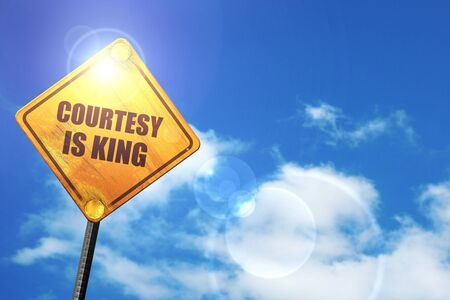 a courtesy: courtesy is king: yellow road sign with a blue sky and white clouds