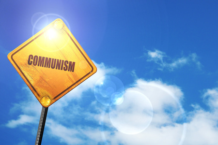 labor strong: communism: yellow road sign with a blue sky and white clouds