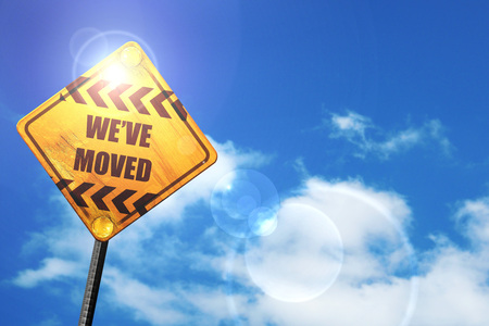 We've moved sign with some soft smooth lines: yellow road sign with a blue sky and white clouds Stock Photo