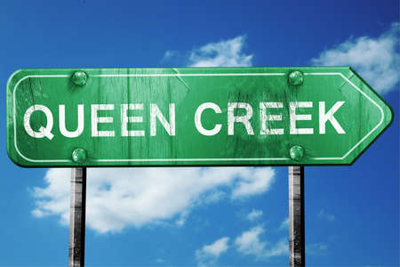 wooden board: queen creek road sign on a blue sky background Stock Photo