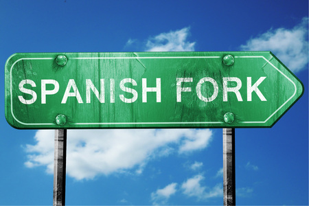 fork in road: spanish fork road sign on a blue sky background