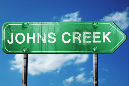 creek: johns creek road sign on a blue sky background Stock Photo