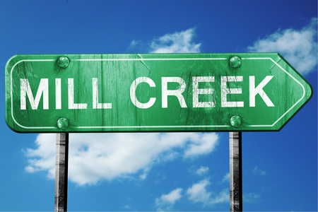 creek: mill creek road sign on a blue sky background