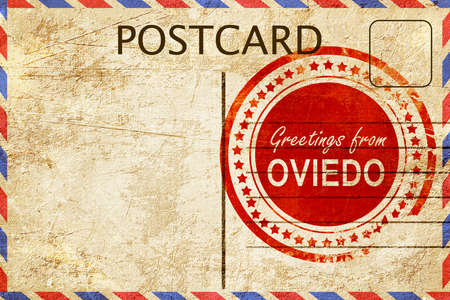 stamped: greetings from oviedo, stamped on a postcard