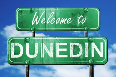 green road sign: Welcome to dunedin green road sign