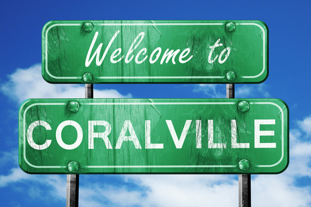 green road sign: Welcome to coralville green road sign