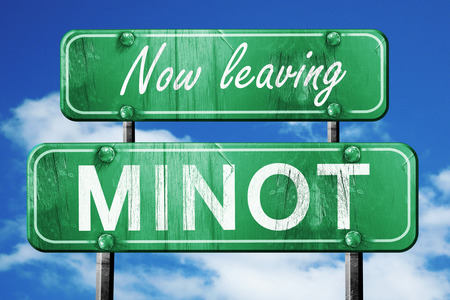 leaving: Now leaving minot road sign with blue sky Stock Photo
