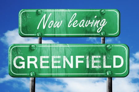 greenfield: Now leaving greenfield road sign with blue sky Stock Photo