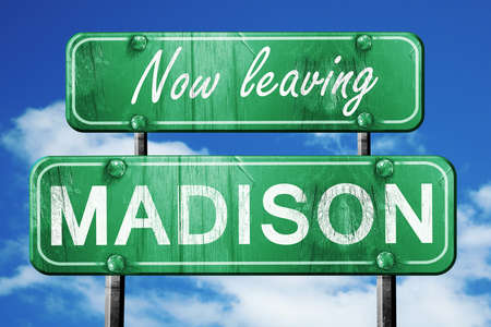leaving: Now leaving madison road sign with blue sky Stock Photo