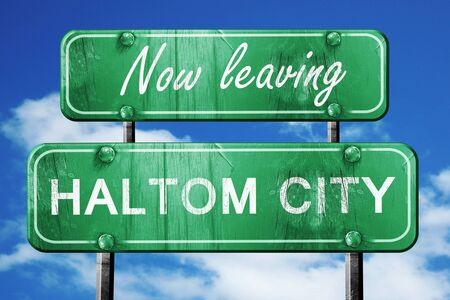 leaving: Now leaving haltom city road sign with blue sky