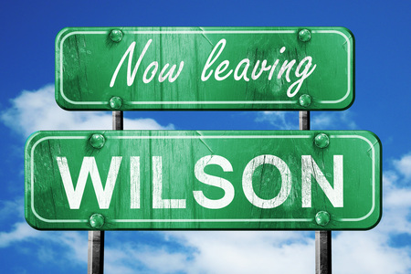 wilson: Now leaving wilson road sign with blue sky Stock Photo