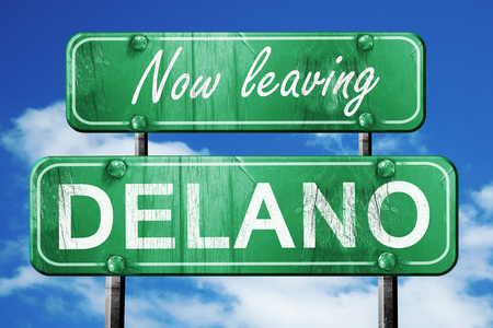 Now leaving delano road sign with blue sky Stock Photo
