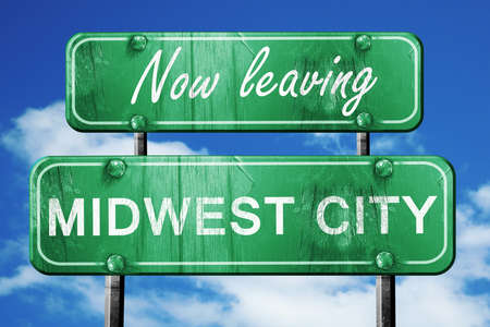 midwest: Now leaving midwest city road sign with blue sky