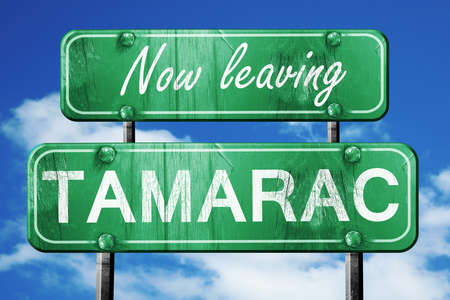 leaving: Now leaving tamarac road sign with blue sky