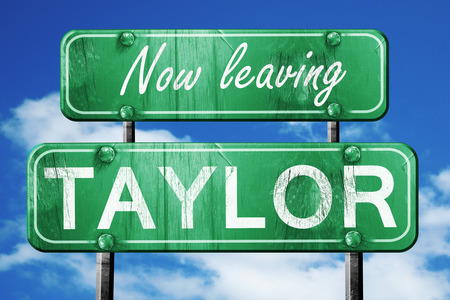taylor: Now leaving taylor road sign with blue sky Stock Photo