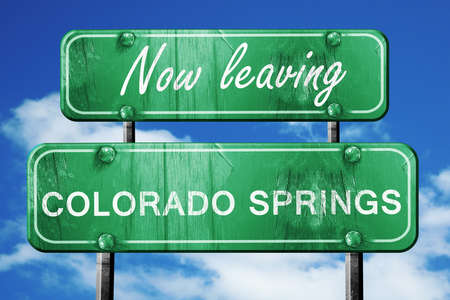 springs: Now leaving colorado springs road sign with blue sky Stock Photo